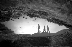 Syrian children are reflected in a puddle at a crowded displaced-persons camp in Aleppo province.