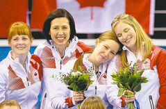 Canada skip Jennifer Jones (right) and third Kaitlyn Lawes rest their heads on each other on the podium with lead Dawn McEwen (left) and second Jill Officer.