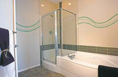 The ensuite features an oval soaker tub and a shower.