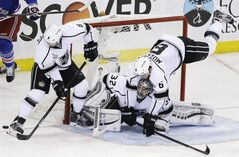 Los Angeles Kings defenseman Jake Muzzin (6) trips over goalie Jonathan Quick (32) as defenseman Drew Doughty (8) helps defend against the New York Rangers in the second period during Game 3 of the NHL hockey Stanley Cup Final, Monday, June 9, 2014, in New York. (AP Photo/Frank Franklin II)