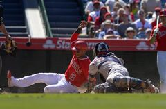 Los Angeles Angels' Erick Aybar, left, is safe at home as Houston Astros catcher Carlos Corporan makes a late tag after Angels' Howie Kendrick grounded into a fielder's choice during the eighth inning of a baseball game on Sunday, July 6, 2014, in Anaheim, Calif. (AP Photo/Mark J. Terrill)