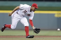 Cincinnati Reds third baseman Kris Negron fields a ground ball hit by Chicago Cubs' Starlin Castro in the first inning of a baseball game, Wednesday, Aug. 27, 2014, in Cincinnati.Negron threw Castro out at first. (AP Photo/Al Behrman)