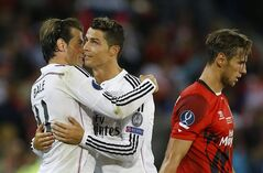Real Madrid's Gareth Bale, left and Cristiano Ronaldo hug as Sevilla's Grzegorz Krychowiak walks off the pitch at the end of the UEFA Super Cup soccer match between Read Madrid and Sevilla at Cardiff City Stadium in Wales Tuesday, Aug. 12, 2014. Real Madrid won the match 2-0. (AP Photo/Kirsty Wigglesworth)