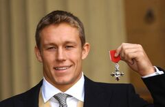FILE - In this Wednesday, Dec. 10, 2003 file photo, England rugby World Cup hero Jonny Wilkinson displays the MBE, Member of the Order of the British Empire, received from Britain's Queen Elizabeth II, outside Buckingham Palace in London. World Cup-winning England flyhalf Jonny Wilkinson announced he will retire from rugby at the end of this season in a statement on Toulon's website posted Monday May 19, 2014. Wilkinson had already retired from international duty but continued playing for French club Toulon. (AP Photo/Stefan Rousseau, Pool, File)