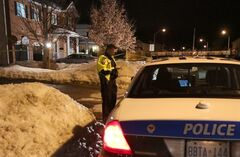 An Ottawa police officer uses his phone at the scene of three deaths in Stittsville, a suburb of Ottawa, on January 14, 2013. THE CANADIAN PRESS/Patrick Doyle