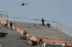 Men work on the stands of Itaquerao stadium in Sao Paulo, Brazil, Thursday, May 8, 2014. The still unfinished stadium will host the World Cup opener match between Brazil and Croatia on June 12. (AP Photo/Andre Penner)