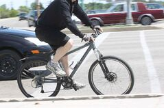 A Cyclist navigates through heavy traffic at Bishop Grandin Boulevard and Pembina Highway Thursday afternoon. On Monday, a cyclist died after being hit by a car on his way to the Winnipeg Blue Bombers game.
