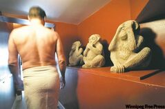 An Aquarius customer walks past 'See No Evil, Hear No Evil, Speak No Evil' statues that symbolize the confidentiality of the bathhouse.