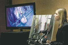 Mercy for Animals Canada's Twyla Francois shows video and still photo taken at Puratone hog farm.