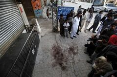 Local residents and members of the news media gather at spot where Nasiruddin Haqqani, a senior leader of the feared militant Haqqani network, was assassinated at an Afghan bakery in the Bhara Kahu area on the outskirts of Islamabad, Pakistan, Monday, Nov. 11, 2013. A Pakistani Taliban commander and an intelligence official say a senior leader of the feared militant Haqqani network has been shot dead in Islamabad. (AP Photo/Anjum Naveed)