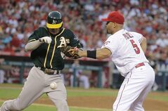 Oakland Athletics' Josh Donaldson, left, takes first base as Los Angeles Angels first baseman Albert Pujols misses a throw from catcher Hank Conger during the fourth inning of a baseball game Saturday, Aug. 30, 2014, in Anaheim, Calif. (AP Photo/Jae C. Hong)