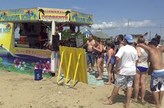 In this July 21, 2014 photo, customers wait to buy treats at George Manko's shave ice concessions trailer in Westerly, R.I. Manko has been cited for defying the town's new ban on street vendors. Town officials said the ban was prompted by safety concerns. A court will now decide. (AP Photo/Jennifer McDermott)