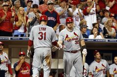 St. Louis Cardinals starting pitcher Lance Lynn, left, is congratulated by Matt Adams after scoring against the San Diego Padres in the fifth inning of a baseball game Tuesday, July 29, 2014, in San Diego. Lynn had singled and scored on a sacrifice fly by Kolten Wong. (AP Photo/Lenny Ignelzi)