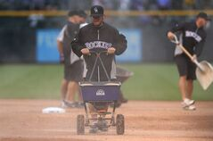 As rains settles in over Coors Field, members of the maintenance crew use a water-absorbing substance on the infield as the Los Angeles Dodgers face the Colorado Rockies in the fourth inning of a baseball game in Denver on Sunday, June 8, 2014. (AP Photo/David Zalubowski)