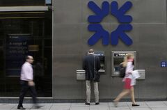 Pedestrians walk past a RBS bank cash machine in London, Aug. 2, 2013. THE CANADIAN PRESS/AP, Alastair Grant
