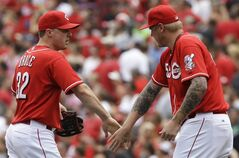 Cincinnati Reds' Jay Bruce, left, is congratulated by starting pitcher Mat Latos, right, after they defeated the Milwaukee Brewers 4-2 in a baseball game, Sunday, July 6, 2014, in Cincinnati. Bruce hit a two-run home run and Latos was the winning pitcher. (AP Photo/Al Behrman)