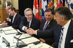 Canada's Finance Minister Joe Oliver, center, shakes hands with Ontario Finance Minister Charles Sousa, right, as Saskatchewan Justice Minister Gordon Wyant second from right, looks on along with British Columbia Finance Minister Mike de Jong, left, and New Brunswick Justice Minister Troy Lifford after signing an agreement to move towards a cooperative capital markets regulatory system at a news conference in Ottawa on Wednesday, July 9, 2014. THE CANADIAN PRESS/Fred Chartrand