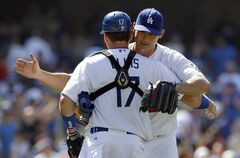 Los Angeles Dodgers relief pitcher Jamey Wright, right, congratulates catcher A.J. Ellis, left, after defeating the St. Louis Cardinals 6-0 in a baseball game on Sunday, June 29, 2014, in Los Angeles. (AP Photo/Alex Gallardo)