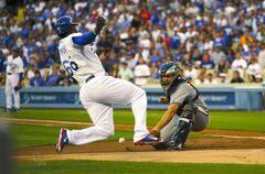 Los Angeles Dodgers' Yasiel Puig, left, scores on a double by Adrian Gonzalez as Atlanta Braves catcher Evan Gattis takes a late throw during the first inning of a baseball game, Thursday, July 31, 2014, in Los Angeles. (AP Photo/Mark J. Terrill)