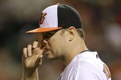 Baltimore Orioles starting pitcher Chris Tillman rubs his nose as he walks back to the mound after Boston Red Sox's Jonathan Herrera singled to load the bases in the fourth inning of a baseball game, Tuesday, June 10, 2014, in Baltimore. (AP Photo/Patrick Semansky)
