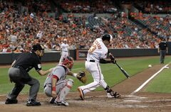 Baltimore Orioles' Manny Machado hits a solo home run in front of Washington Nationals catcher Wilson Ramos and home plate umpire Dan Iassogna in the fourth inning of an interleague baseball game, Wednesday, July 9, 2014, in Baltimore. (AP Photo/Patrick Semansky)