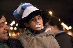 A child shows his support for Uruguay player Luis Suarez, by wearing toy plastic vampire teeth, as he awaits the arrival of Suarez at Carrasco International Airport in the outskirts of Montevideo, Uruguay, Thursday, June 26, 2014. The Uruguay forward, widely regarded as one of the best players in the world, was banned by FIFA from all football for four months on Thursday for biting an Italian opponent in an incident that marred the team's victory and progression to the second round. (AP Photo/Matilde Campodonico)