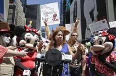 Lucia Gomez, center, executive director of La Fuente, speaks during a press conference, Tuesday, Aug. 19, 2014 at Times Square in New York. Gomez lead the gathering that called for the fair treatment and the right for performers to work as costumed characters. Gomez said,
