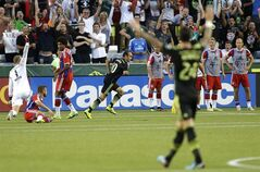 Los Angeles Galaxy forward Landon Donovan, center rear, celebrates after he scored the go-ahead goal on Bayern Munich goalkeeper Manuel Neuer, left, in the second half of the MLS All-Star soccer game, Wednesday, Aug. 6, 2014, in Portland, Ore. The MLS All-Stars won 2-1. (AP Photo/Ted S. Warren)