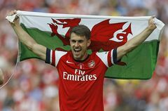 Arsenal's Aaron Ramsey celebrates holding the Welsh national flag after his team won the English FA Cup final soccer match between Arsenal and Hull City at Wembley Stadium in London, Saturday, May 17, 2014. Arsenal won 3-2 after extra-time. (AP Photo/Kirsty Wigglesworth)