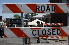 Authorities block the road into the Mayfair Mews apartment complex where an F/A-18D Hornet jet crashed Friday in Virginia Beach, Va., as the investigation continues, on Saturday, April 7, 2012. (AP Photo/Virginian-Pilot, Preston Gannaway) MAGS OUT