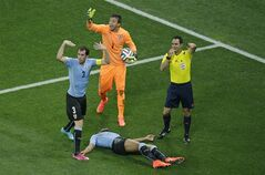 Uruguay's Diego Godin, goalkeeper Fernando Muslera and referee Carlos Velasco Carballo from Spain, from left, call for medical support as Uruguay's Alvaro Pereira lies on the floor during the group D World Cup soccer match between Uruguay and England at the Itaquerao Stadium in Sao Paulo, Brazil, Thursday, June 19, 2014. (AP Photo/Michael Sohn)