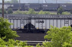 ADVANCE FOR MONDAY, JULY 28, 2014, AT 12:01 A.M. AND THEREAFTER - In this May 22, 2014, photo, empty train cars, front, sit in a yard after having their loads of coal unloaded at Norfolk Southern's Lamberts Point coal terminal in Norfolk, Va. As the Obama administration weans the U.S. off dirty fuels blamed for global warming, energy companies have been sending more of America's unwanted energy leftovers to other parts of the world. It's a global shell game on fossil fuels that at the very least makes the U.S. appear to be making more progress on global warming than it actually is, because it shifts some of the pollution, and the burden for cleaning it up, onto another country's balance sheet. (AP Photo/Patrick Semansky)