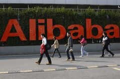 In this March 17, 2014 photo, people walk past a company logo at the headquarters of Alibaba Group in Hangzhou, in eastern China's Zhejiang province. Even before Alibaba went online, its founder talked about making the fledgling e-commerce company a global player. (AP Photo) CHINA OUT