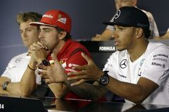 Mercedes driver Lewis Hamilton of Britain talks and gestures flanked by Ferrari driver Fernando Alonso of Spain, and Mercedes driver Nico Rosberg of Germany during a news conference at the Monza racetrack, in Monza, Italy , Thursday, Sept. 4 , 2014. The Formula one race will be held on Sunday. (AP Photo/Luca Bruno)
