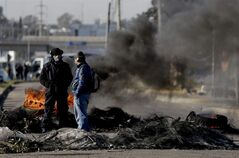 Two men stand next to a barricade of burning tires, meant as a supportive gesture to fellow workers who continue to work despite being laid off, outside the entrance of the R.R. Donnelley & Sons printing plant, on the outskirts of Buenos Aires, Argentina, Thursday, Aug. 14, 2014. About 200 workers decided to keep working until union leaders, in talks with the Labor Ministry, find a solution to reverse the plant layoffs. (AP Photo/Natacha Pisarenko)
