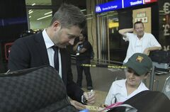 Australia's cricket captain Michael Clarke, left, signs a small cricket bat for unidentified fan during their arrival at OR Tambo International Airport in Johannesburg, South Africa, Wednesday, Jan. 29, 2013, for their Test cricket tour against South Africa. (AP Photo/ Themba Hadebe)