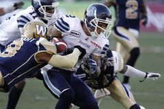 Winnipeg Blue Bombers' Brandon Stewart tackles Toronto Argonauts' Chad Owens early in the first quarter Saturday at Canad Inns Stadium.