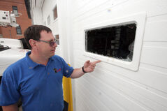 All Points Electric Ltd. owner Darren Wright points to dried blood left on a garage window after the break-in.