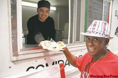 Jorge Torres serves tacos to customer Marcus Leon at Torres' and his business partner Ian Bowman's El Torrito taco truck on Broadway.