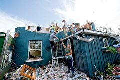 Family and friends salvage what is left of a home that was demolished by a tornado in Goderich, Ont, on Sunday.