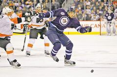 Winnipeg Jets' Evander Kane drives past  Philadelphia Flyers' Andrej Meszaros during  an NHL game Feb. 21