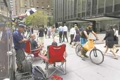 Media members wait outside JPMorgan Chase's New York headquarters Friday.