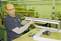 Employee Tony Benias shows thickness and interior bracing of PVC frame material at The Window Factory in Selkirk.