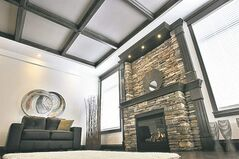 A gas fireplace is framed with cultured stone and features a dark oak mantel and trim to create a rich ambience