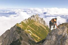 A mountain hiker transcending the Garsellikopf approaches the Three Sisters mountains, seen in background, near Planken, Liechtenstein.