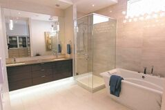 One of thee-and-a-half bathrooms features a a six-foot soaker tub tucked and a five-foot tempered glass/tile shower.
