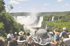 Tourists take pictures of the Iguazu Falls, which has an annual peak flow of some 6,500 cubic meters a second.