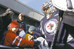 Goalie Ondrej Pavelec signs an autograph for fan Alison Giebler, 8, of New York, before the team held their outdoor practice.