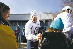 Olli Jokinen signs for a couple of young fans who showed up for the team�s practice.