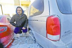 Rupinder Dhaliwal stands on a block of ice next to his vehicle in the frozen parking lot.